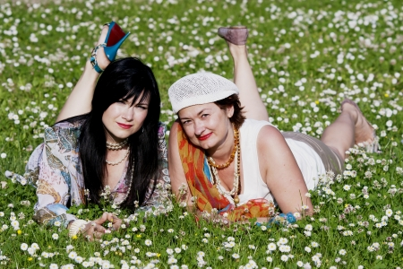 Two pleasant ladies have a rest on a floral lawn photo