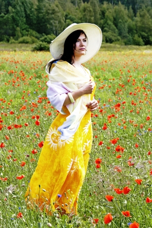 Cute brunette in a hat and yellow dress on the poppy field photo