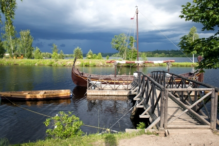 Retro wooden boats near a wooden pier on the river before a thunderstorm photo