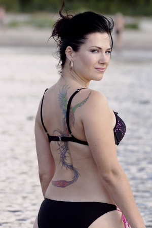 body paint sexy: Girl on a beach with the sexy tattoo of fire-bird Stock Photo