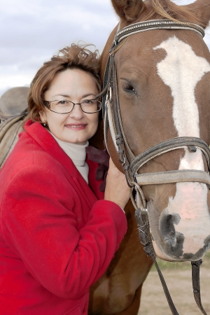 Portrait happy smiling woman with horse after a walk astride photo