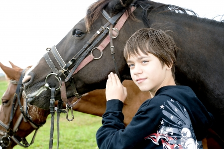 Young boy pets a horse after a walk photo