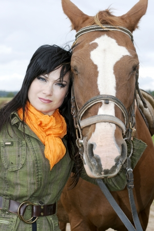 Portrait of beautiful brunette with horse after a walk astride photo