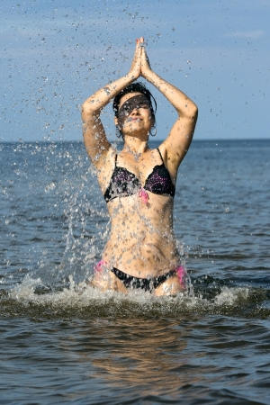 Woman doing yoga in the sparks of water on the Baltic sea photo