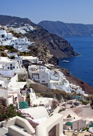 Small wonderful white houses located on the volcanic mountains of Santorini, Oia, Greece photo