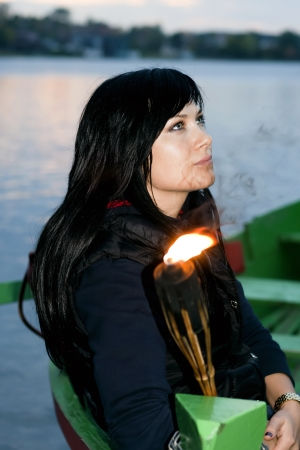 conflagrant: Girl in a boat with a conflagrant tiki torch ashore lake in Trakai, Lithuania