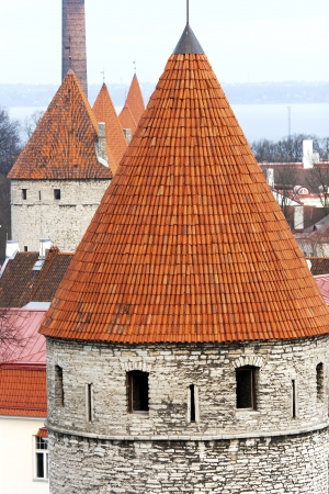 Old stone tower under a red tile of Old Tallinn with a view on the Baltic sea photo