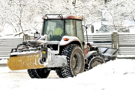 Snow cleaning  tractor clears paths in a park photo