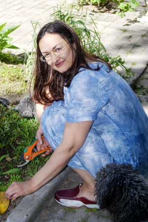 pruning scissors: Nice lady pruning with a secateurs scissors a dry branches