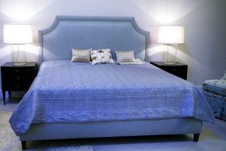 bedspread: Large bed under a blue bedspread and two  lamps