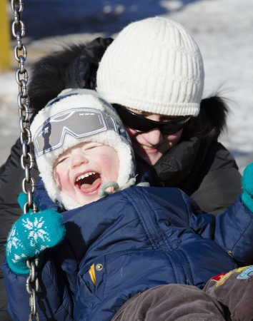 Happy laughing boy with a mother on swinging photo