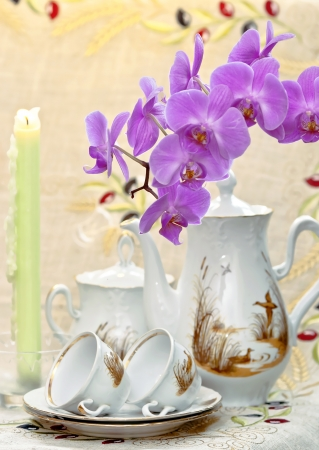 conflagrant: Coffee service for breakfast with flower of living orchid and conflagrant candles Stock Photo