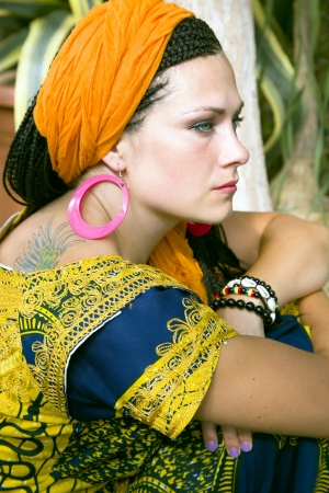 Beautiful blue-eyed woman with the african pigtails and by a tattoo on a shoulder photo