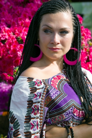 Intent look of beautiful blue - eyed woman with the african pigtails on a background blooming azalea photo