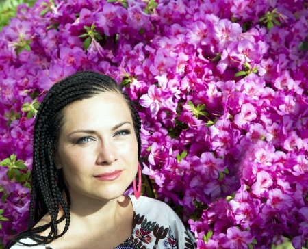 Beautiful blue-eyed woman with the african pigtails on a background blooming pink azaleas photo