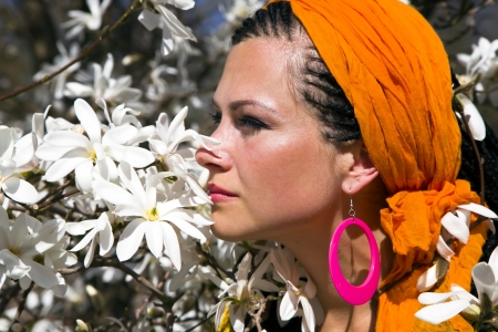 Beautiful blue-eyed woman with the african pigtails smell the branches of flowering magnolia photo