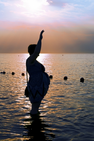 Silhouette of a Pregnant woman at the beach during sunset on Baltic sea photo