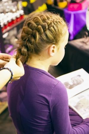 Cute little lady is plait a fashionable braid on an exhibition Baltic Beauti 2013, 02 November Riga, Latvia Editorial