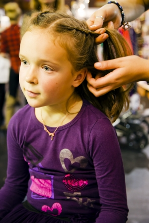 latvia girls: Cute little lady is plait a fashionable braid on an exhibition Baltic Beauti 2013, 02 November Riga, Latvia Editorial