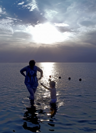 Mother with a little son in the swashing on Baltic sea  waters at sunset photo