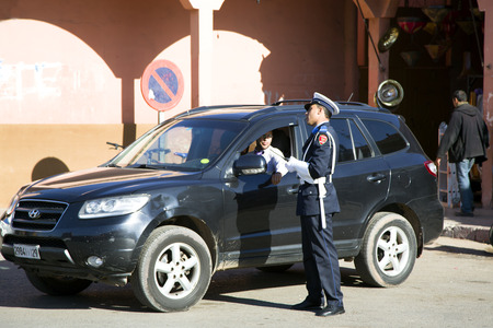 A policeman explains to a road the traveller of Marrakesh in old Medina, Morocco