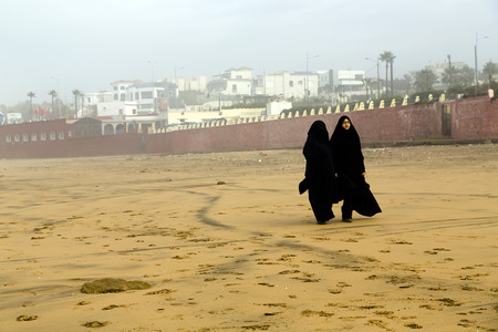 purdah: CASABLANCA, MOROCCO 27 DECEMBER, 2013  Two Arabic women are in a yashmak go on the beach of the Atlantic ocean in Casablanca