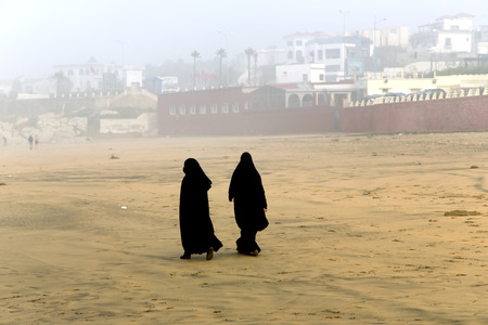 purdah:  Two Arabic women are in a yashmak go on the beach of the Atlantic ocean in Casablanca
