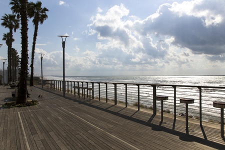 yam israel: Wooden promenade with high bar chairs and view the Mediterranean sea in Bat-Yam, Israel