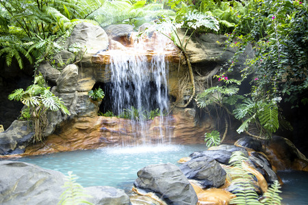 Swimming pool with a waterfall and hot thermal water at the modern luxury hotel The Springs Resort and Spa in Costa Rica, Central America