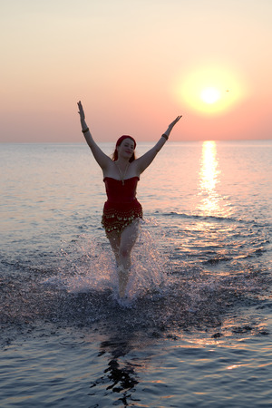 Pretty young woman runs in the Baltic sea surrounded by splashing water on sunset background photo