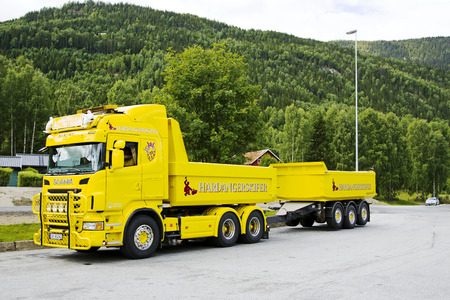 expects:  Yellow cargo truck with a trailer expects loading