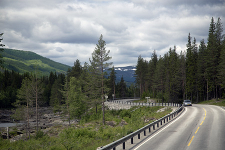 Scenic empty road among the dense forests of in beautiful mountains of Norway. photo