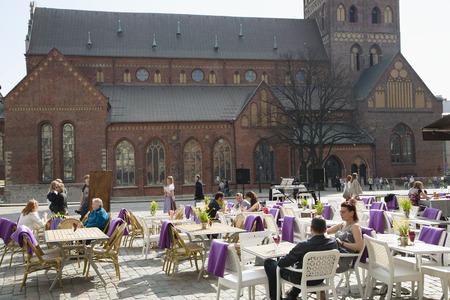alongside: LATVIA, RIGA, MAY, 24, 2014 - Summer patio alongside to Dome Cathedral in Riga, Latvia