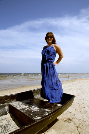 the stands: Cute miniature brunette stands in a wooden boat on a background the Baltic sea Stock Photo