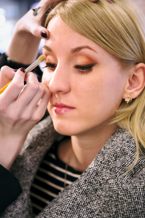 does: Professional visagiste does a make-up attractive girl