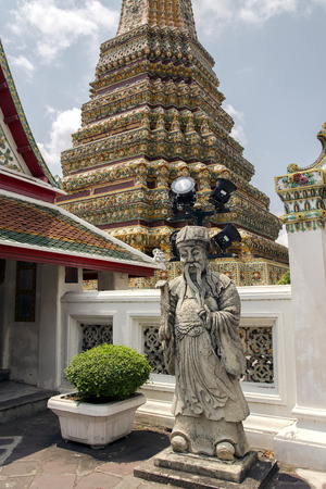 includes: Chinese Rock Giant at Wat Phra Kaew, Emerald Buddha Temple, that also includes the former residence of the Thai monarch, the Grand Palace. Bangkok, Thailand.