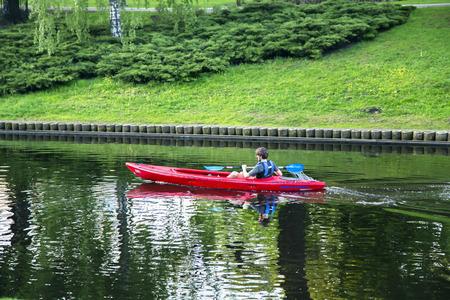 kayaker: LATVIA, RIGA, JULY, 18, 2015 - Single kayaker swims on a city channel in Riga, Latvia