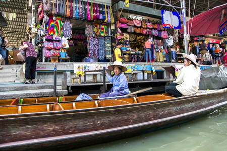 congested: THAILAND, BANGKOK, MARCH, 26, 2015 - Damnoen Saduak Floating Market in Bangkok, Thailand. The colorfully clad merchants at these lively markets paddle along congested canals in sturdy canoes laden with fresh fruit and vegetables to sell