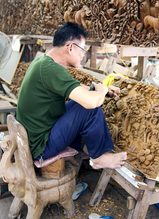 out of production: THAILAND, BANGKOK, MARCH, 26, 2015 - Master woodcarver cuts out a picture from a teak. The production of things from a teak is very important for a country. Thailand