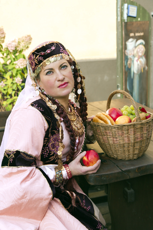 latvia girls: Portrait beautiful lady in the Armenian folk clothing and handwork ethnic necklace with a wicker basket in Old Riga, Latvia Stock Photo