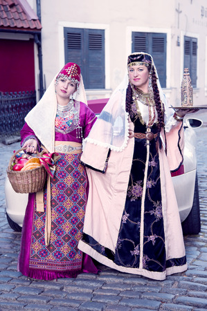 latvia girls: Two cute ladies are in the Armenian suits and by a small basket with fresh fruit in Riga Stock Photo