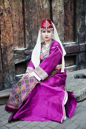 trabajo manual: señora hermosa del retrato en la ropa tradicional armenio y trabajo hecho a mano collar étnico en el casco antiguo de Riga, Letonia