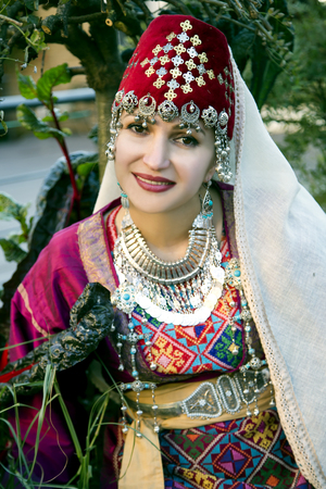 latvia girls: Portrait beautiful lady in the Armenian folk clothing and handwork ethnic necklace on a background midget trees in Riga, Latvia Stock Photo