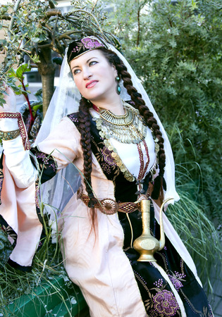 Portrait beautiful lady in the Armenian folk clothing and handwork ethnic necklace on a background midget trees in Riga, Latvia Stock Photo