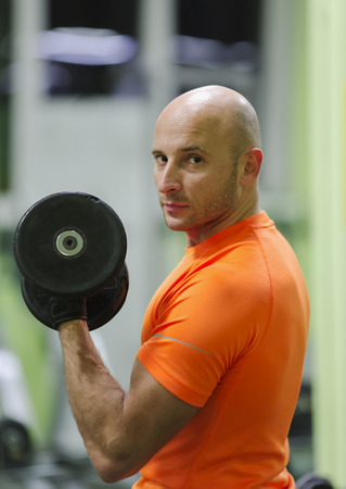 engaged: Sporting man is engaged in training in fitness center in a gym