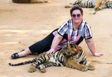 Woman with a little tiger are in Wat Pa Luangta Bua Yannasampanno Forest Monastery, Tiger Temple, Kanchanaburi, Thailand.