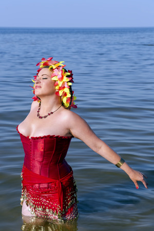 latvia girls: Beautiful woman in a red corset and floral chaplet in the Baltic sea, Jurmala, Latvia Stock Photo