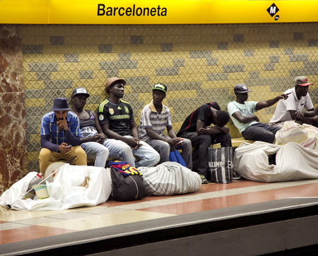 counterfeit: SPAIN, BARCELONA, JUNE, 28, 2015 - Street Vendors with large bales are waiting for a train in the subway in Barcelona, Spain. Street Vendors sell their merchandise, much of which is counterfeit. Editorial