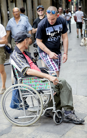 severely: SPAIN, BARCELONA, JUNE, 27, 2015 - Man in a wheelchair asks for help to passers in the Gothic Quarter, Barcelona, Catalonia, Spain