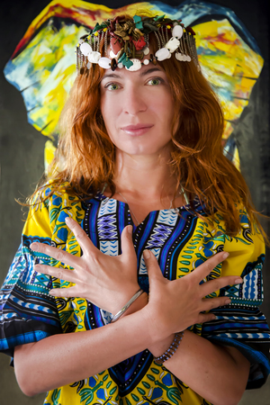 clothing model: Red-haired beautiful girl with green eyes in the African national costume on a background pattern with bright colors in Arusha, Tanzania, Africa